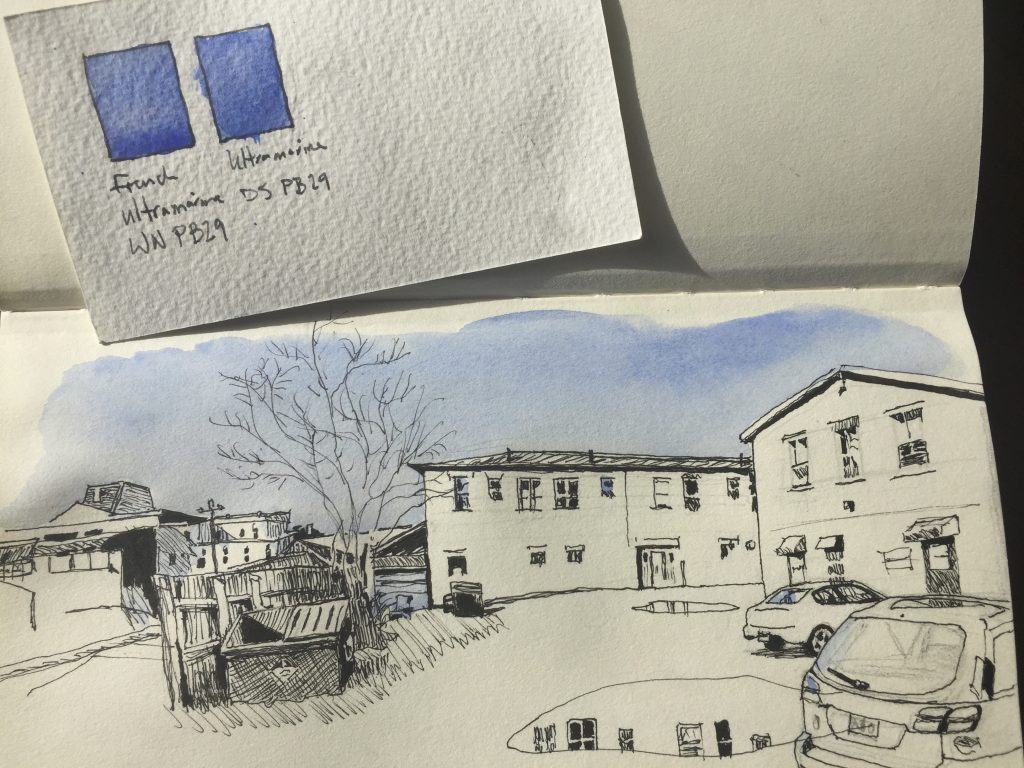 Winsor & Newton vs. Daniel Smith ultramarine swatches over a sketch of Struts Gallery in Sackville, New Brunswick